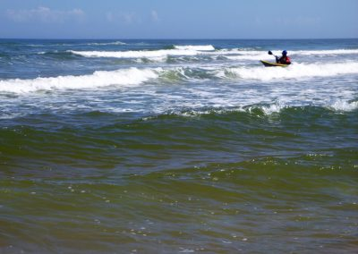 kayaker crossing the surf zone