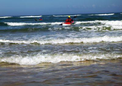 kayaker paddling out through surf