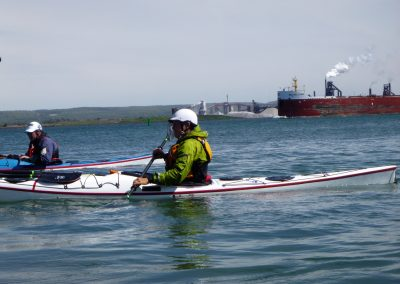 bow of freighter and kayakers